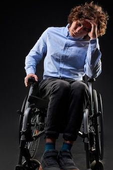 L'homme handicapé déprimé n'a aucun sens dans la vie, il est assis sur un fauteuil roulant, mécontent de quelque chose, s'assoit en regardant vers le bas. isolé sur fond noir