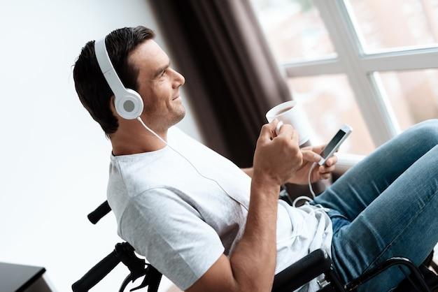 Un homme handicapé écoute de la musique et boit du café