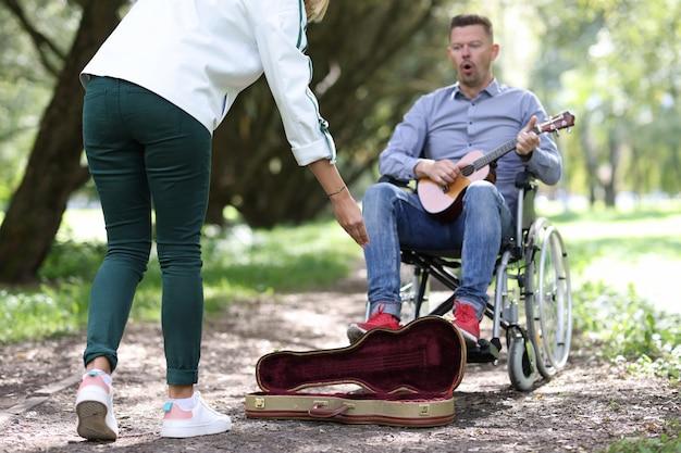 Un homme handicapé en fauteuil roulant joue de la guitare dans un parc et gagne de l'argent musicien de rue handicapé