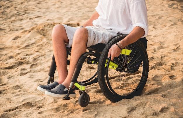 Homme handicapé en fauteuil roulant sur la plage.