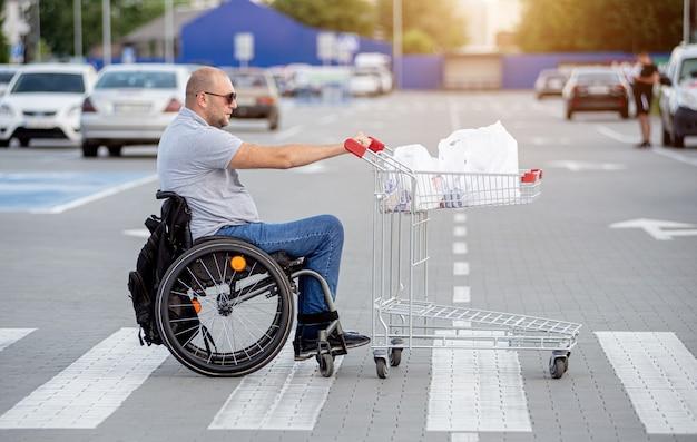 Homme handicapé en fauteuil roulant poussant le chariot devant lui au parking du supermarché