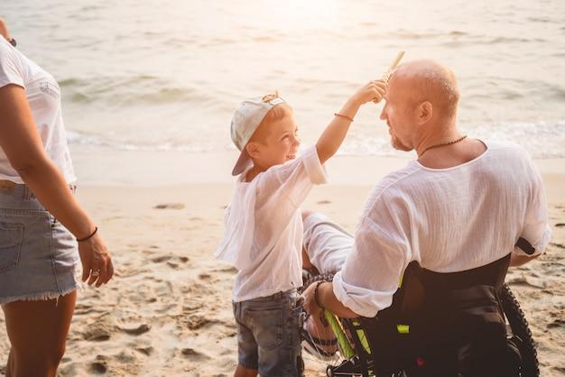 Homme handicapé en fauteuil roulant avec sa famille sur la plage.