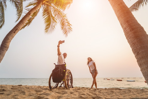 Homme handicapé en fauteuil roulant avec sa femme sur la plage.
