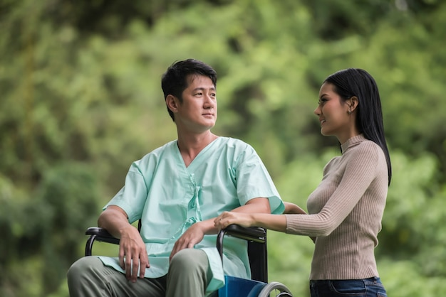 Homme handicapé en fauteuil roulant et sa petite amie dans le parc