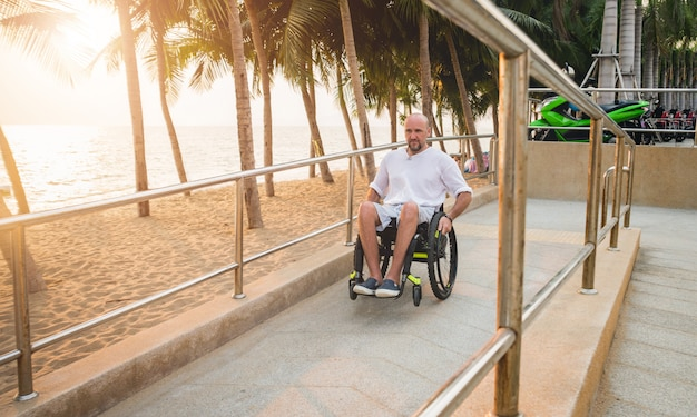 Homme handicapé en fauteuil roulant se déplace sur une rampe d'accès à la plage.
