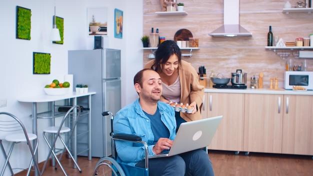 Homme handicapé en fauteuil roulant utilisant un ordinateur portable dans la cuisine et sa femme se tient à côté de lui. homme d'entreprise avec paralysie handicap handicap handicapé difficultés à travailler après accident ayant internet sur
