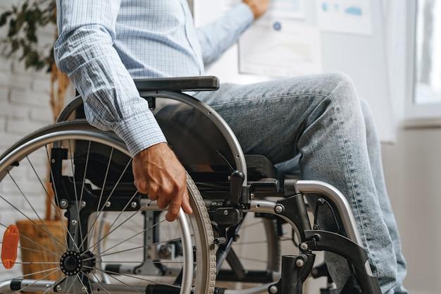 Homme handicapé méconnaissable assis dans un fauteuil roulant