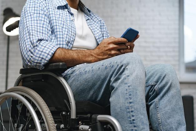 Homme handicapé de race mixte assis dans un fauteuil roulant et utilisant un smartphone
