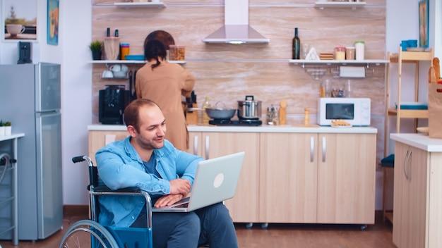 Homme handicapé saluant la vidéoconférence à l'aide d'un ordinateur portable dans la cuisine. homme d'entreprise avec paralysie handicap handicap handicapé difficultés à travailler après accident ayant internet appel vidéo en ligne conf