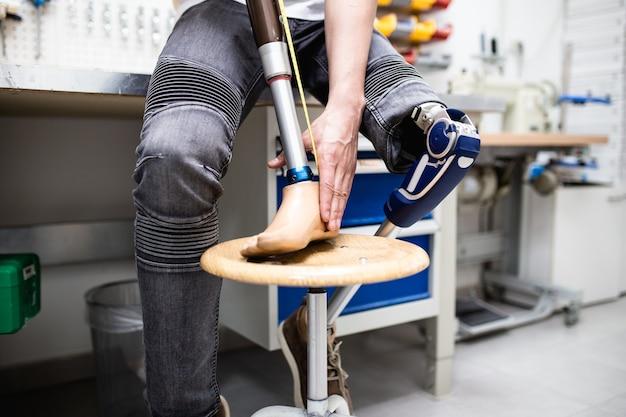 Homme handicapé travaillant dans un magasin d'amputés pour la production de pièces d'extrémité prothétiques.