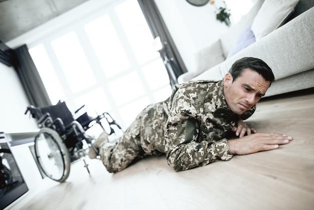 Un homme handicapé en uniforme est tombé d'un fauteuil roulant