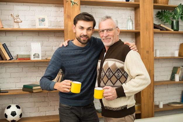 Homme heureux âgé, étreignant avec jeune homme avec des tasses près d'étagères