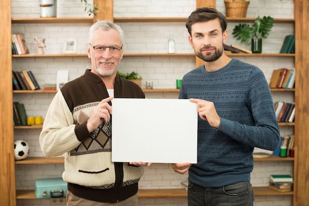 Homme heureux âgé et jeune homme souriant tenant un papier