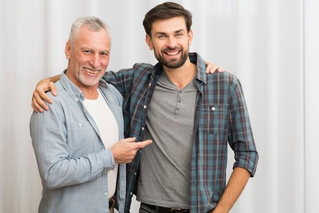 Homme heureux âgé montrant et étreignant avec jeune homme souriant