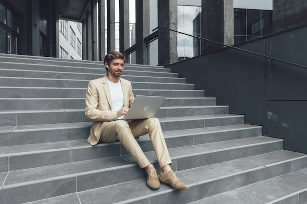 Homme heureux attrayant vêtu de vêtements formels assis sur les escaliers à l'extérieur et travaillant sur un ordinateur portable personnel