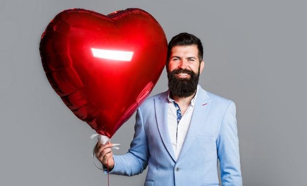 Homme heureux avec des ballons à air en forme de coeur. la saint-valentin. coeur rouge.