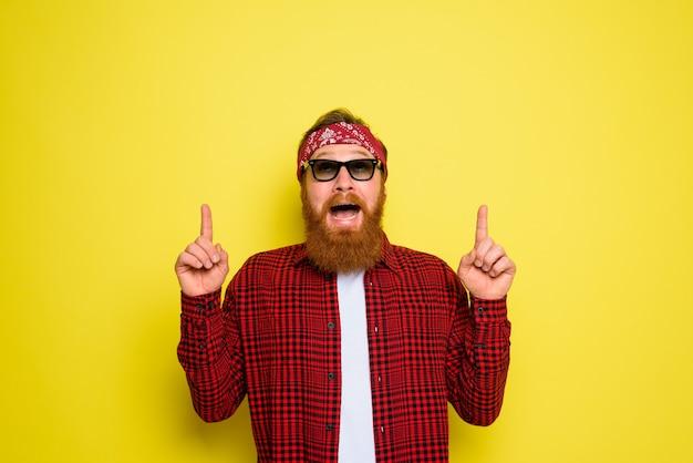 L'homme heureux avec la barbe et le bandana dans les cris de tête indique quelque chose