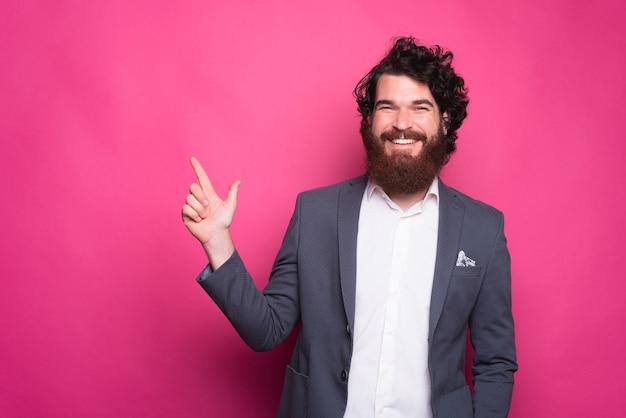 Homme heureux avec barbe en souriant décontracté et pointant vers l'arrière-plan