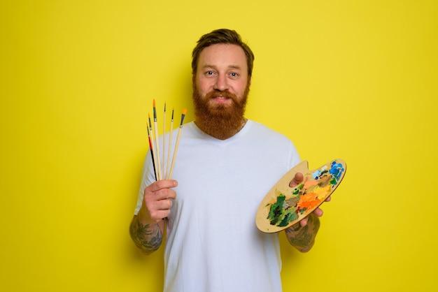 L'homme heureux avec la barbe et le tatouage est prêt à dessiner avec des brosses