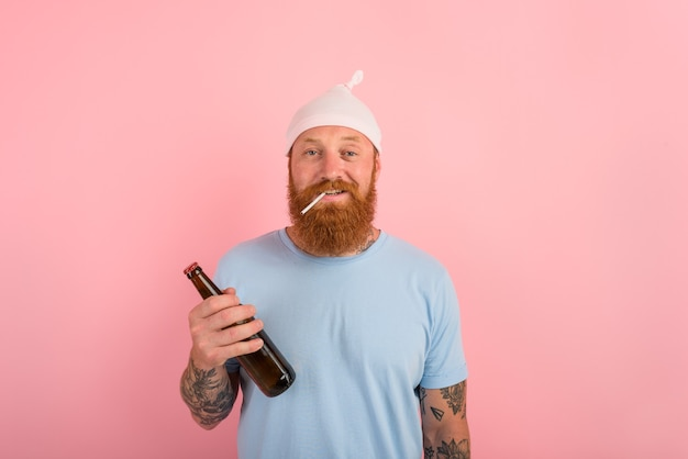 Un homme heureux avec de la barbe et des tatouages agit comme un petit nouveau-né avec de la bière à la main