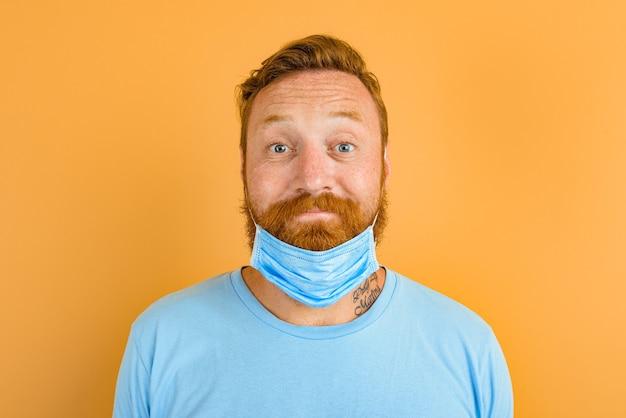 Un homme heureux avec de la barbe et des tatouages enlève le masque pour covid-19