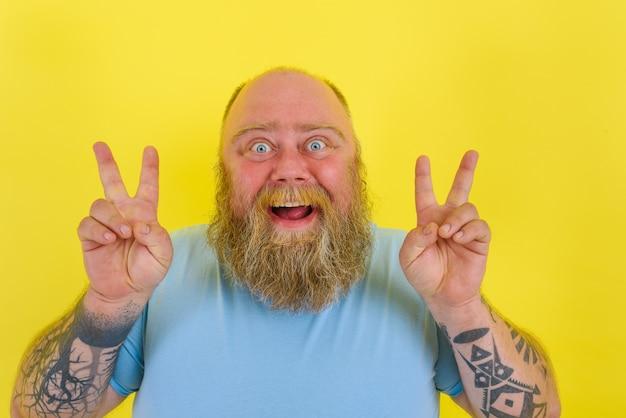 Un homme heureux avec une barbe et des tatouages fait un geste gagnant avec les mains