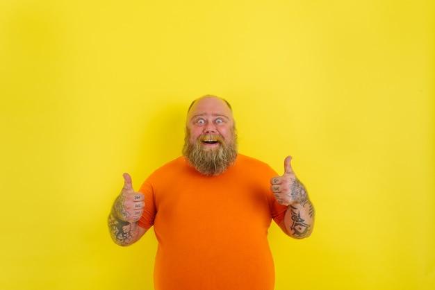 L'homme heureux avec la barbe et les tatouages fait un geste positif avec les mains