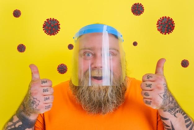L'homme heureux avec la barbe et les tatouages porte un écran facial protecteur contre le covid
