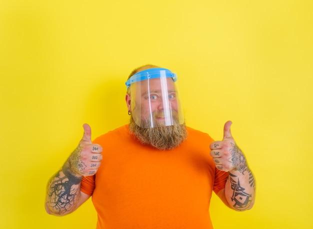 Un homme heureux avec de la barbe et des tatouages porte un écran facial de protection contre le virus covid-19