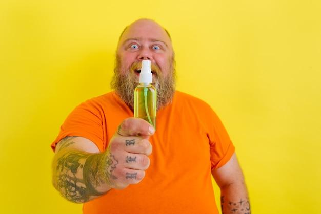 Un homme heureux avec de la barbe et des tatouages tient un nettoyant pour les mains contre le covid