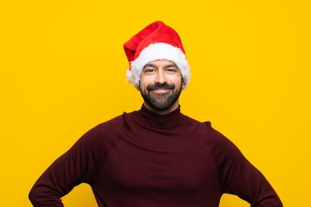 Homme heureux avec un chapeau de noël sur fond jaune isolé