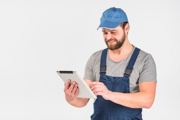 Homme heureux en combinaison avec tablette