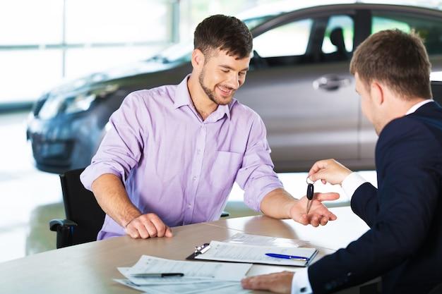 Homme heureux avec un concessionnaire automobile dans un salon de l'auto ou un salon