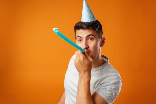 Homme heureux avec cône de fête soufflant dans la corne du parti sur fond jaune