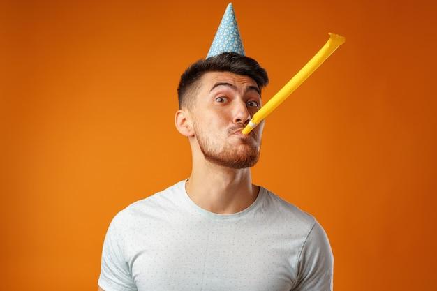 Homme heureux avec cône de fête soufflant dans la corne de fête