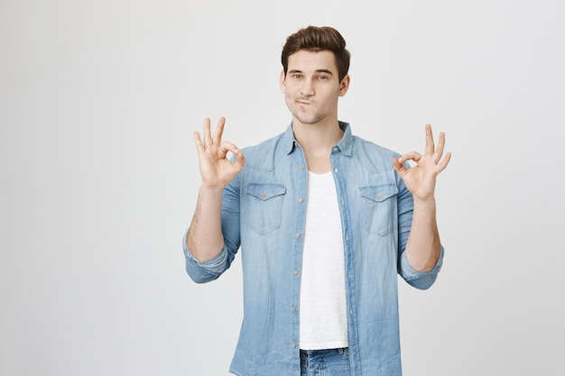 Un homme heureux et confiant montre un geste correct, approuve ou garantit