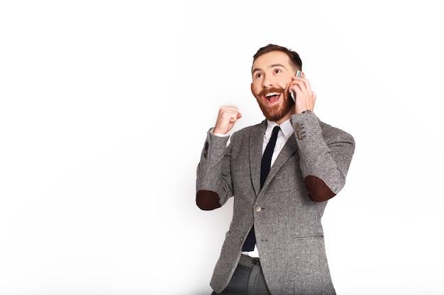 Homme heureux en costume gris parle au téléphone