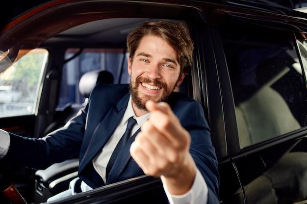 Homme heureux en costume regarde par la fenêtre de la voiture et fait des gestes avec ses mains