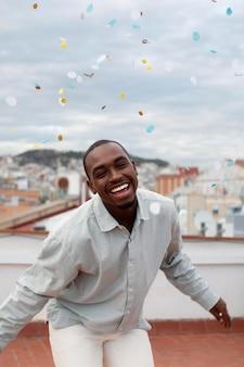 Homme heureux de coup moyen avec des confettis