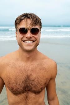 Homme heureux de coup moyen avec des lunettes de soleil