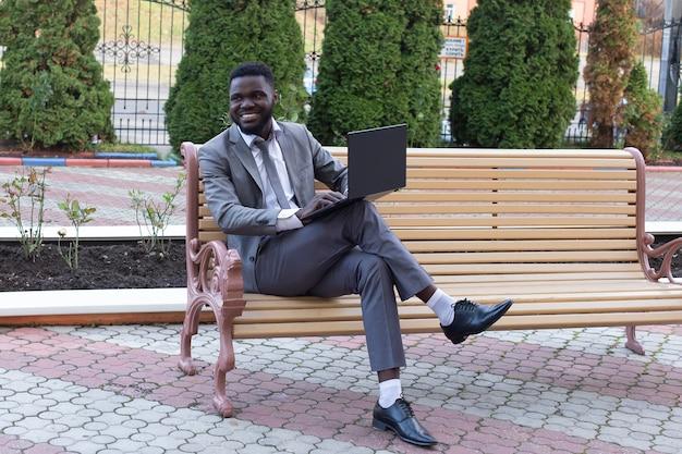 L'homme heureux dans la rue avec un ordinateur portable, à la pige