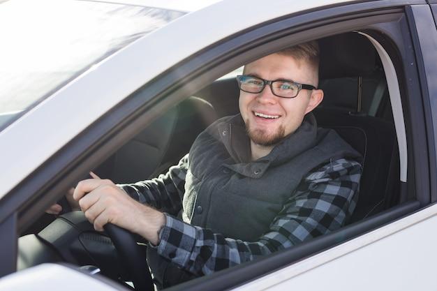 Homme heureux élégant attrayant dans une bonne voiture blanche.