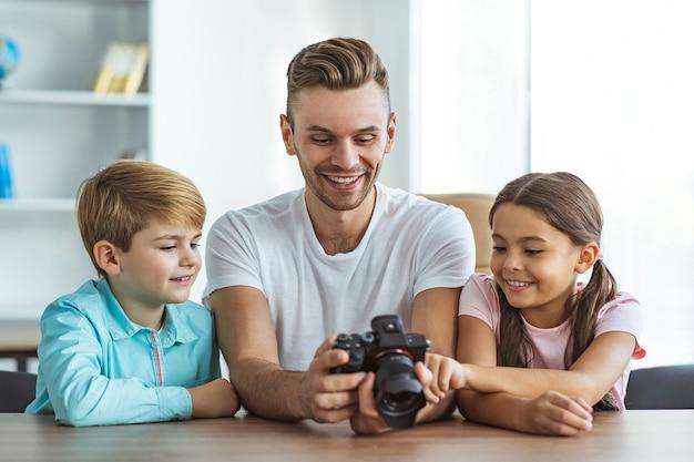 L'homme heureux avec des enfants tenant un appareil photo à la table