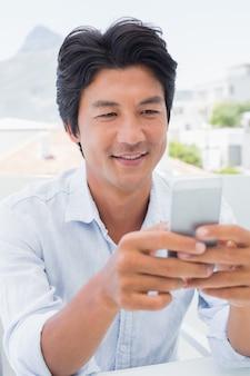 Homme heureux, envoyer des sms sur le téléphone