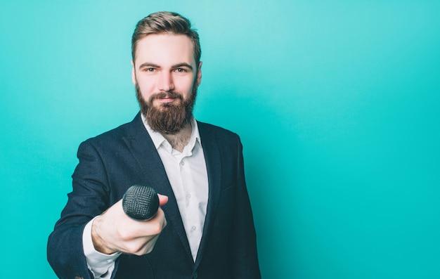 Un homme heureux est debout et regarde droit devant tout en tenant un microphone