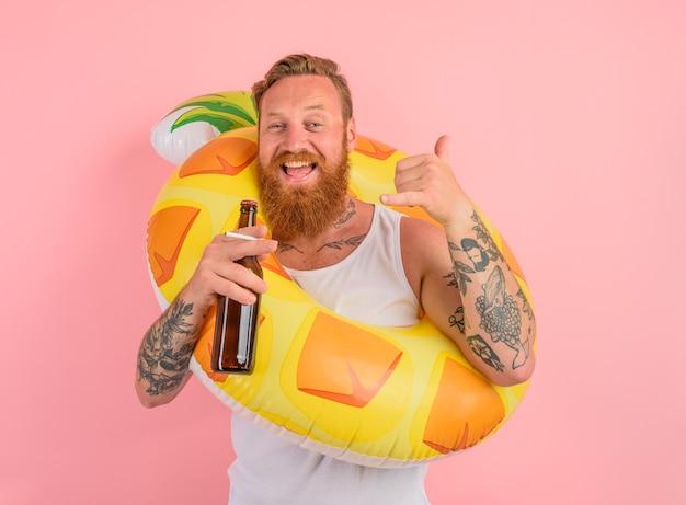 Un homme heureux est prêt à nager avec une bouée de sauvetage en beignet avec de la bière et une cigarette à la main