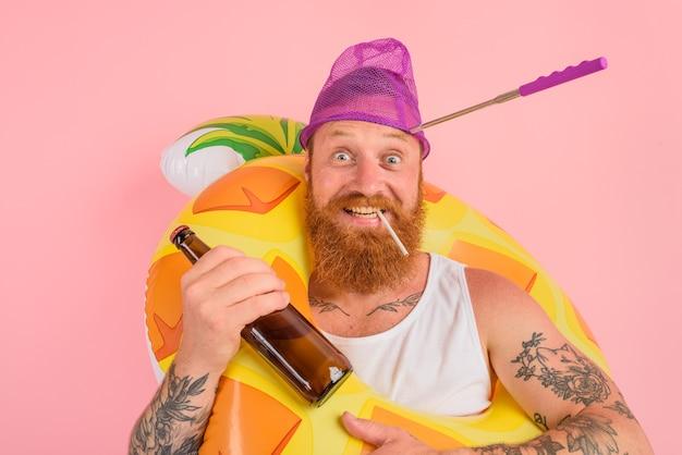 L'homme heureux est prêt à nager avec une bouée de sauvetage de beignet avec de la bière et de la cigarette