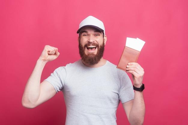 Un homme heureux est prêt pour le voyage, tenant des billets et un passeport