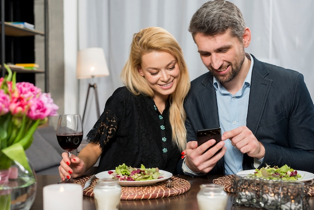 Homme heureux et femme joyeuse à l'aide de smartphone à table