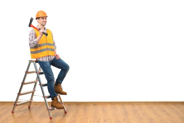 L'homme heureux avec la hache se tenant sur l'échelle sur le fond blanc de mur